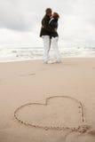 Coração no beijo novo dos amantes da areia dois Imagens de Stock