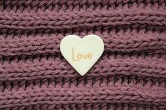 Coração plástico branco com palavra do amor em um fundo violeta feito malha da textura fotografia de stock royalty free
