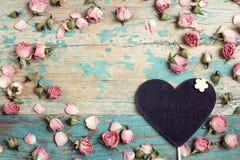 Coração-quadro-negro com as flores cor-de-rosa pequenas na turquesa wo velho imagem de stock royalty free