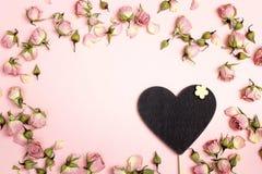Coração-quadro-negro vazio com as rosas secas pequenas no fundo cor-de-rosa imagens de stock royalty free