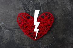 Coração quebrado ao meio em um fundo escuro Fotos de Stock