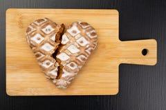 Coração quebrado do pão-de-espécie na mesa de cozinha Os bolos doces são decorados belamente com crosta de gelo imagens de stock