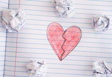 Coração quebrado na folha do caderno com algumas bolas de papel amarrotadas sobre Imagem de Stock