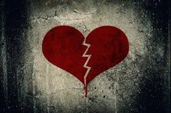 Coração quebrado pintado no fundo da parede do cimento do grunge - ame o engodo fotos de stock