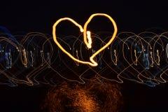Coração tirado com luz na noite com exposição longa na reflexão escura do fundo e da água fotos de stock
