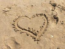 Coração tirado na areia da praia Menina de Alemanha e menino do croata com dicionário Fotos de Stock