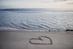 Coração tirado na areia na praia pelo mar fotos de stock