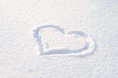 Coração tirado na neve branca fresca em um dia ensolarado Imagens de Stock