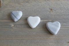 Coração três de pedra no fundo de madeira Foto de Stock