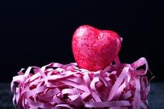 Coração vermelho brilhante com uma palha de papel em um fundo preto Imagem de Stock