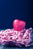 Coração vermelho brilhante com uma palha de papel em um fundo preto toned Fotografia de Stock Royalty Free