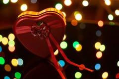 Coração vermelho com uma curva, em um fundo escuro com luzes, um presente para o dia de Valentim fotos de stock royalty free