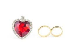 Coração vermelho da joia e dois anéis dourados Fotografia de Stock Royalty Free