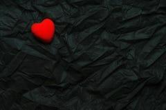 Coração vermelho da vista superior no fundo preto enrugado da textura O dia de Valentim e conceito felizes do amor Cartão românti fotografia de stock royalty free