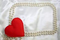 Coração vermelho de matéria têxtil no canto do quadro das pérolas no backgroud do branco de cetim Tema do dia do casamento ou dos Fotografia de Stock Royalty Free