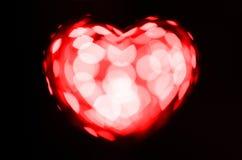 Coração vermelho do bokeh no fundo preto Imagens de Stock Royalty Free