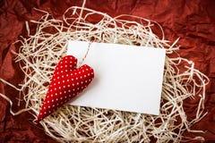 Coração vermelho do brinquedo e cartão vazio na palha fotos de stock royalty free