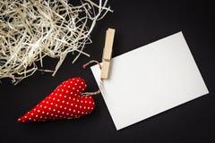 Coração vermelho do brinquedo e cartão vazio no preto foto de stock royalty free