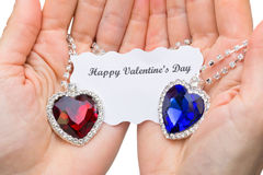 Coração vermelho e azul da joia com o cartão do Valentim nas mãos Fotos de Stock