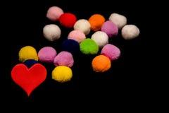 Coração vermelho e bolas peluches coloridas no fundo preto Imagens de Stock Royalty Free