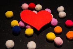 Coração vermelho e bolas peluches coloridas no fundo preto Foto de Stock Royalty Free