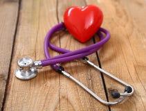 Coração vermelho e um estetoscópio médico na mesa Imagens de Stock