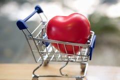 Coração vermelho em um carrinho de compras azul Dia do ` s do Valentim, amor de compra Foto de Stock Royalty Free