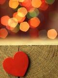 Coração vermelho na borda de uma tabela de madeira Imagens de Stock