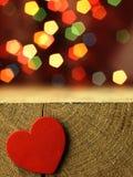 Coração vermelho na borda de uma tabela de madeira Imagem de Stock