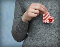 Coração vermelho na mão da mulher no fundo azul Imagem de Stock