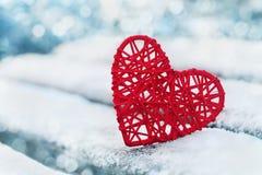 Coração vermelho na neve com fundo do bokeh Cartão do dia dos Valentim inverno do amor Imagens de Stock