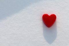 Coração vermelho na neve com luz do sol Fotografia de Stock
