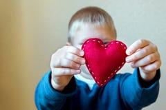 Coração vermelho nas mãos da criança Fotos de Stock