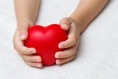Coração vermelho nas mãos da palma do bebê Imagens de Stock Royalty Free