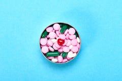 Coração vermelho pequeno com comprimidos multi-coloridos em um fundo azul fotos de stock royalty free