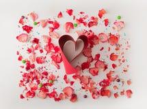 Coração vermelho pequeno feito da fita vermelha, no fundo branco com pétalas cor-de-rosa A composição para temas gosta do amor, d Imagens de Stock Royalty Free