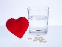 Coração, vidro da água e comprimidos Imagem de Stock