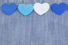 Corações azuis no fundo da sarja de Nimes Fotos de Stock