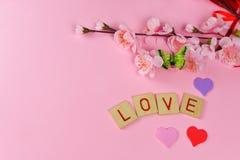 Corações bonitos de letras vermelhas com amor em um fundo cor-de-rosa Fotos de Stock Royalty Free