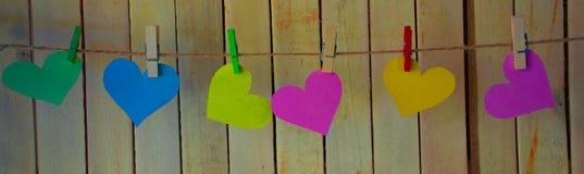 Corações coloridos bonitos em um fundo do woodhung em pregadores de roupa para uma corda bonita foto de stock