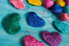 Corações coloridos com bolas da linha no backgr de madeira azul fotos de stock royalty free