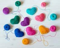 Corações coloridos com bolas da linha no fundo de madeira branco fotos de stock royalty free