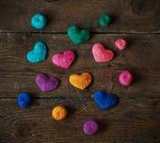 Corações coloridos com bolas da linha no fundo de madeira gasto velho imagens de stock