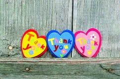 Corações coloridos no fundo de madeira Fotos de Stock