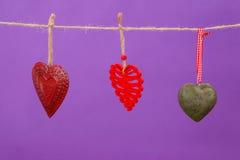 Corações com os projetos diferentes que penduram na corda Imagens de Stock