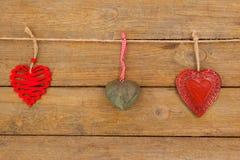 Corações com os projetos diferentes que penduram na corda Foto de Stock