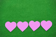 Corações cor-de-rosa que estão apertando a braçadeira de madeira Suspensão sobre à grama Imagem de Stock Royalty Free