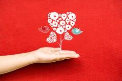 Corações da árvore e pássaros dos pares em uma mão Imagens de Stock Royalty Free