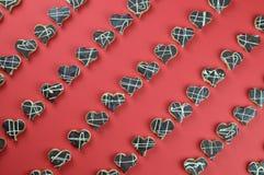 Corações da cookie nas fileiras no vermelho Fotos de Stock Royalty Free