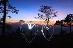 corações da luz dois do desenho pela lanterna elétrica no ar na floresta antes do nascer do sol Foto de Stock Royalty Free
